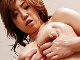 Gorgeous Japanese slut Naho oils up her pretty body and then fingers her hairy muff